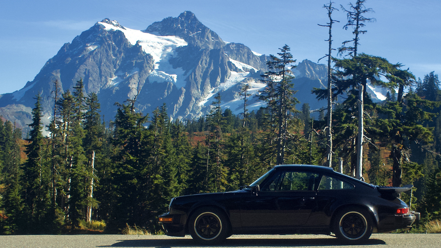 A black vintage 911 in front of a dramatic mountain vista